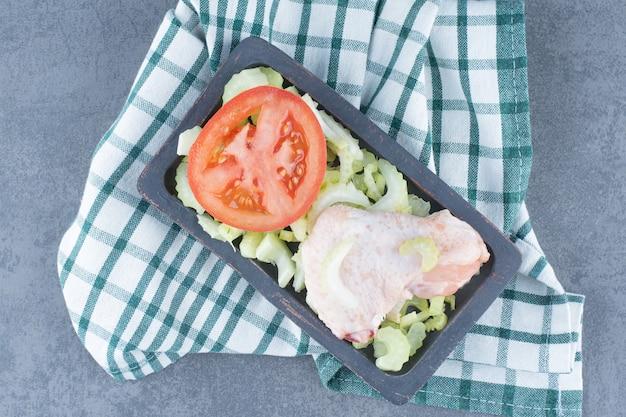 Ongekookte kippenvleugels en tomaat op zwarte plaat.