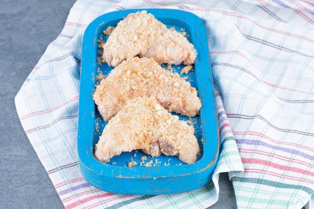 Ongekookte kippenvleugels met broodkruimels op blauw bord.