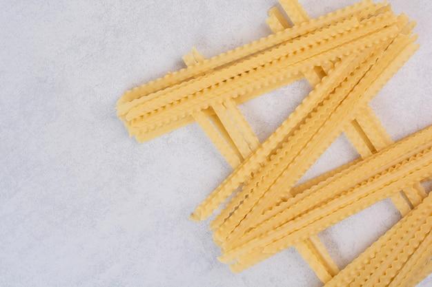 Ongekookte lange pasta op marmeren tafel.