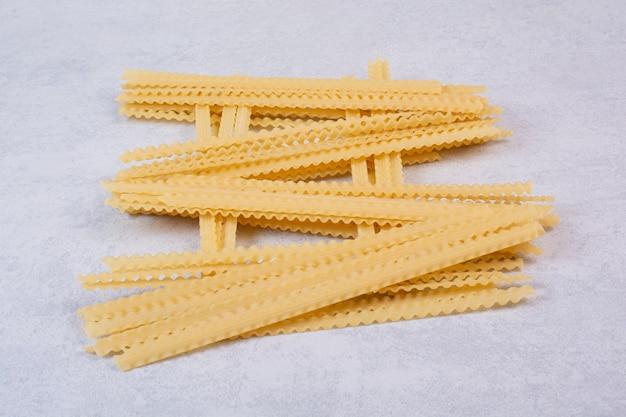 Ongekookte lange pasta op stenen oppervlak