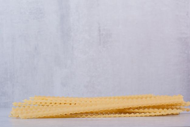 Ongekookte lange pasta op stenen tafel