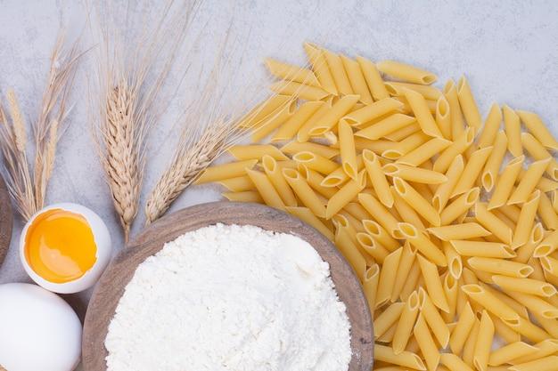 Ongekookte macaroni met dooier en bloem op houten