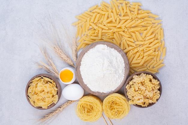 Ongekookte macaroni op houten kom met dooier en bloem