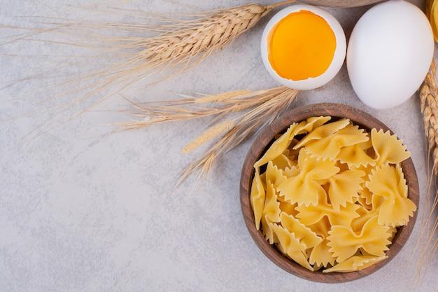 Ongekookte macaroni op houten kom met dooier en bloem.
