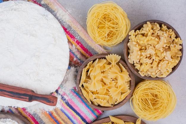 Ongekookte macaroni op houten kommen met dooier en bloem