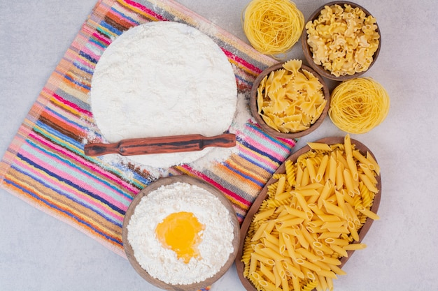 Ongekookte macaroni op houten kommen met dooier en bloem.