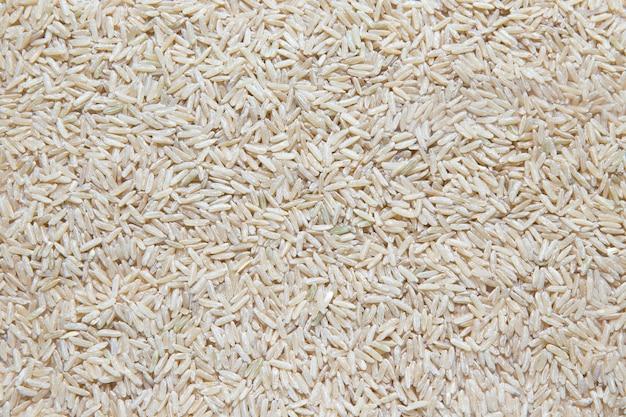 Ongekookte ongepelde rijst die op witte achtergrond wordt geïsoleerd.
