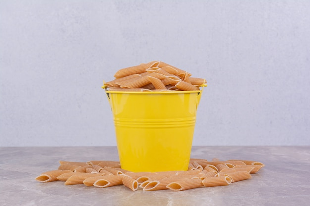 Ongekookte pasta in een gele metalen emmer.