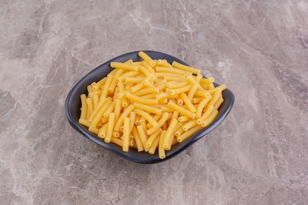 Ongekookte pasta in een zwarte keramische kom op het marmer.