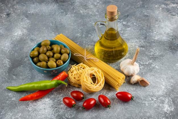 Ongekookte pasta, olie en verse groenten op stenen oppervlak.
