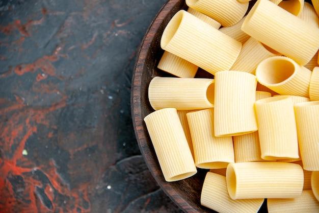 Ongekookte pasta's in de pot op zwarte tafel