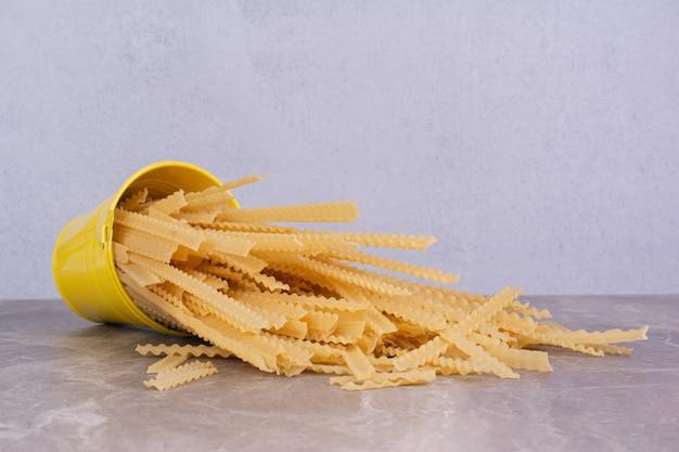 Ongekookte pasta's in een gele metalen containeremmer