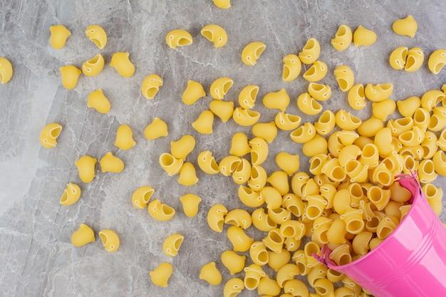 Ongekookte pasta's in een roze metalen emmer.