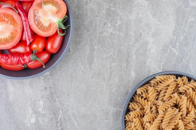 Ongekookte pasta's met kerstomaatjes en chilipepers in een zwarte pan