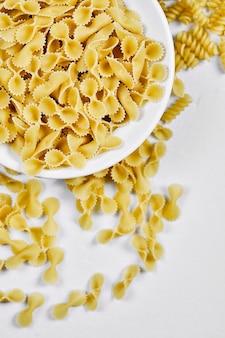 Ongekookte pasta's op witte tafel.