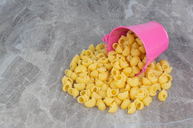 Ongekookte pasta's uit een roze metalen emmer