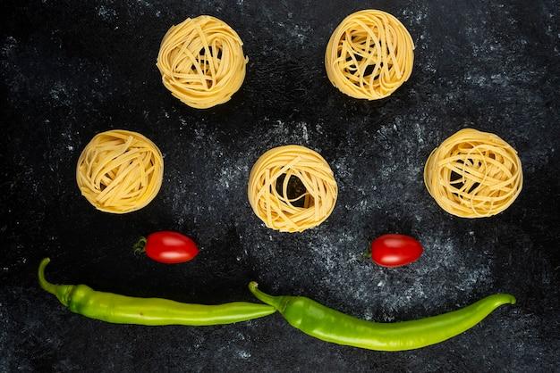 Ongekookte pastanesten en groenten op marmer.