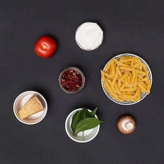 Ongekookte penne pasta en ingrediënt gerangschikt op aanrecht