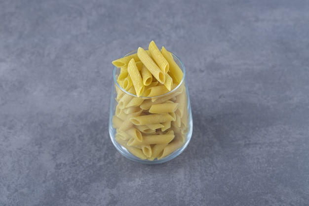 Ongekookte penne pasta in glas op stenen achtergrond.