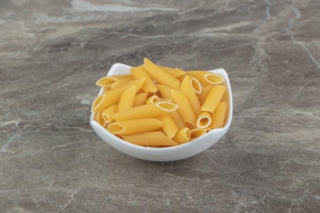 Ongekookte penne pasta in witte kom