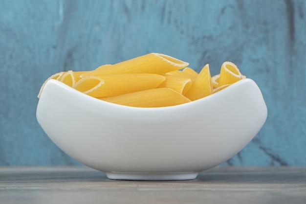 Ongekookte penne pasta in witte kom.