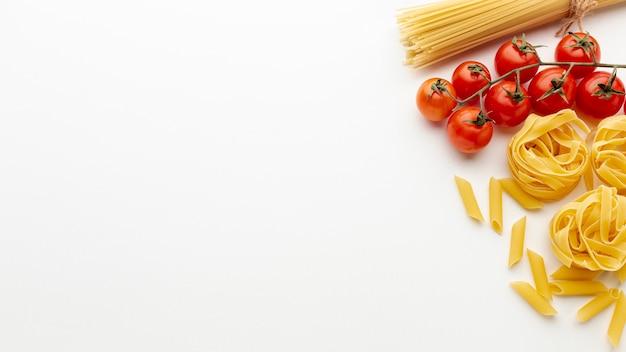Ongekookte penne tagliatelle spaghetti en tomaten met kopie ruimte