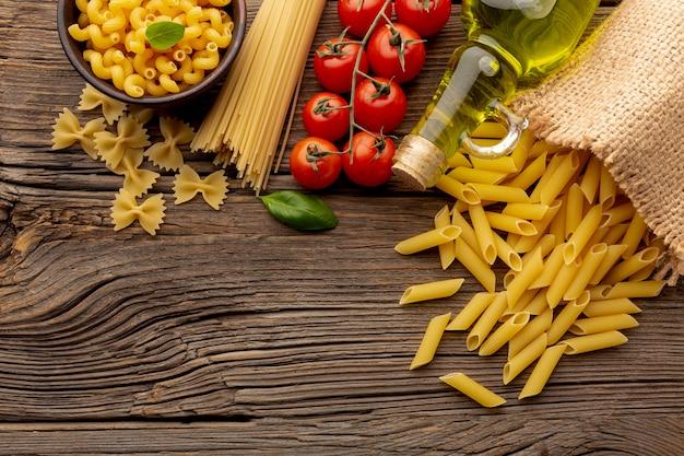 Ongekookte pennespaghetti farfalle tomaten en olijfolie op houten lijst met exemplaarruimte