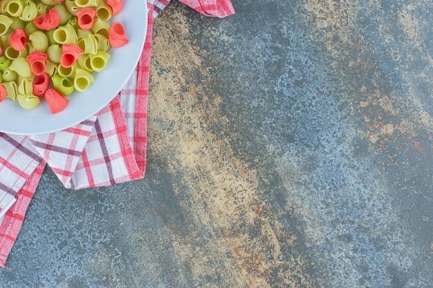 Ongekookte pipe rigate pasta in plaat op de theedoek, op het marmeren oppervlak.