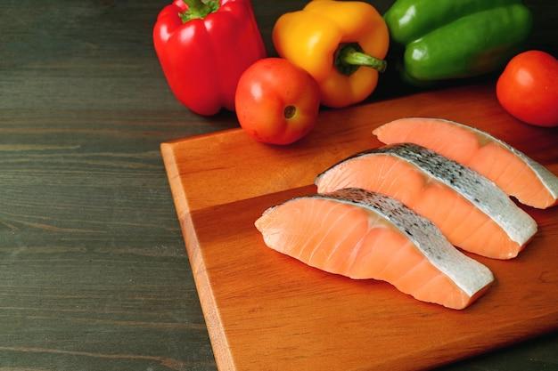 Ongekookte rauwe gesneden zalm op een houten snijplank met verse kleurrijke groenten