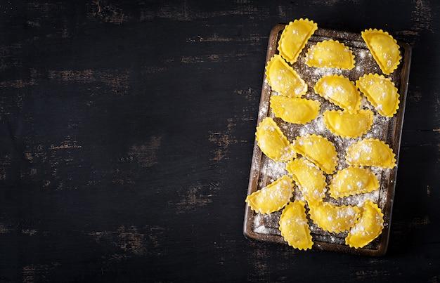 Ongekookte ravioli op tafel. italiaanse keuken. bovenaanzicht achtergrond met copyspace