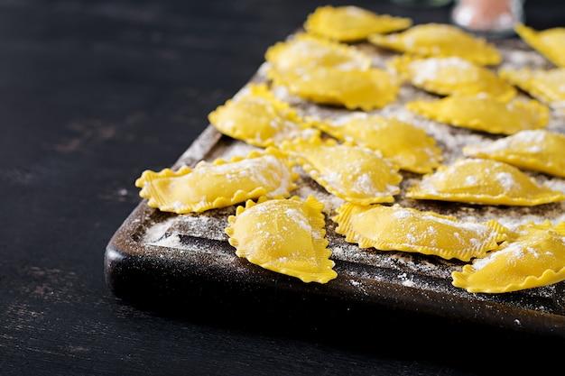 Ongekookte ravioli op tafel. italiaanse keuken.