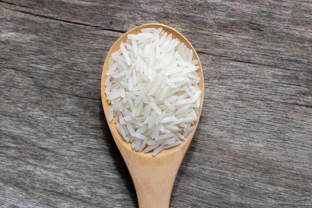 Ongekookte rijst in houten lepel