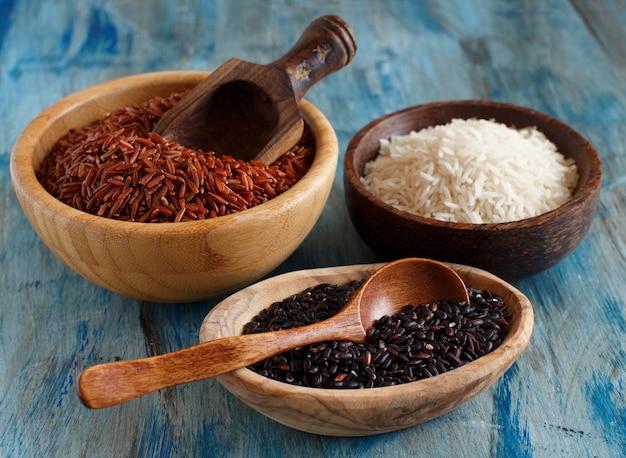 Ongekookte rijst in kommen met houten lepels op tafel