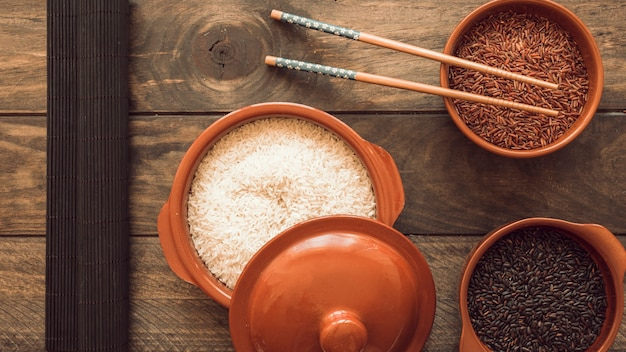 Ongekookte rijstkorrelskommen met eetstokjes op houten lijst