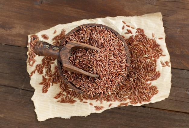 Ongekookte rode rijst in een kom met een houten lepel op de mening van het lijstbovenkant