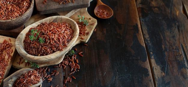 Ongekookte rode rijst in een kom met een houten lepel op tafel