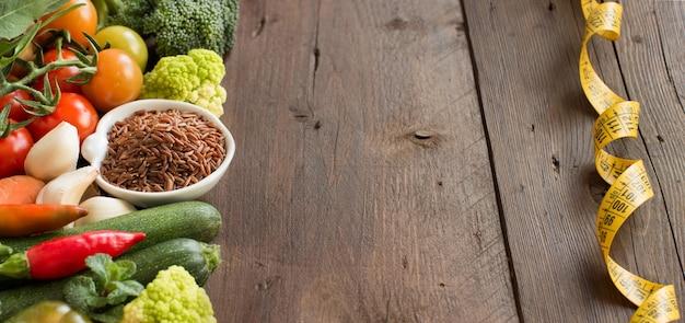 Ongekookte rode rijst in een kom met groenten en meetlint op hout met exemplaarruimte