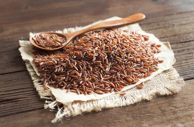 Ongekookte rode rijst met een houten lepel dichte omhooggaand