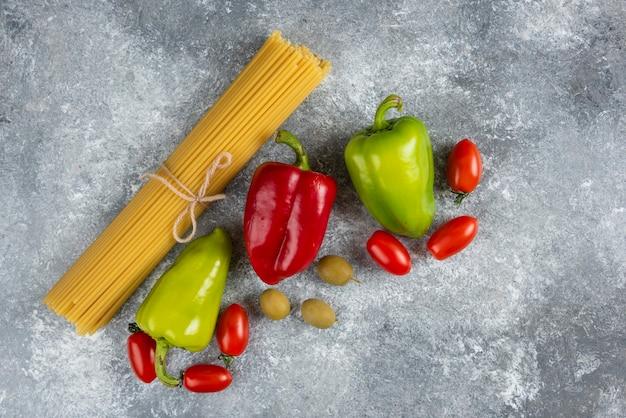 Ongekookte spaghetti en diverse groenten op steenoppervlak.