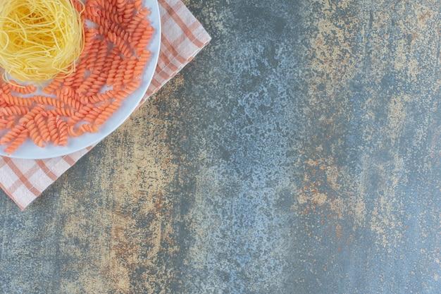 Ongekookte spaghetti en fusilli pasta in kom op handdoek, op de marmeren achtergrond.