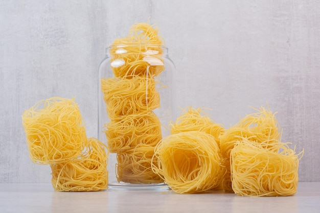 Ongekookte spaghetti nesten op marmeren tafel met pot.
