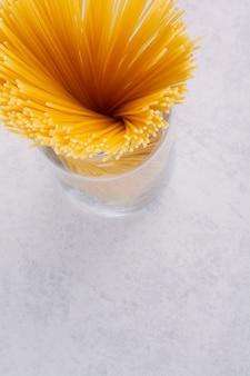 Ongekookte spaghetti pasta in glazen pot