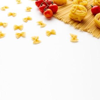 Ongekookte spaghetti tagliatelle farfalle en tomaten met kopie ruimte