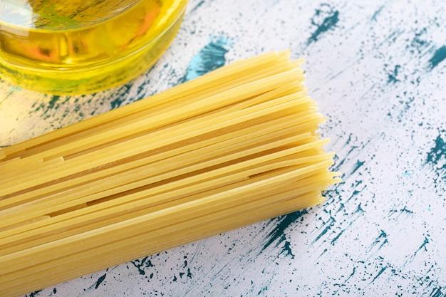 Ongekookte spaghettideegwaren met oliefles op wit.