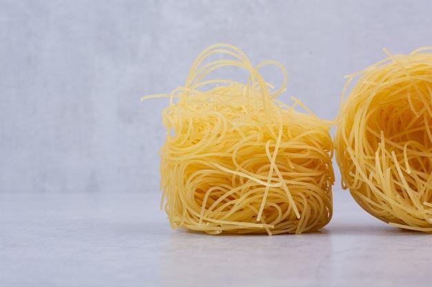 Ongekookte spaghettinesten op steenoppervlakte