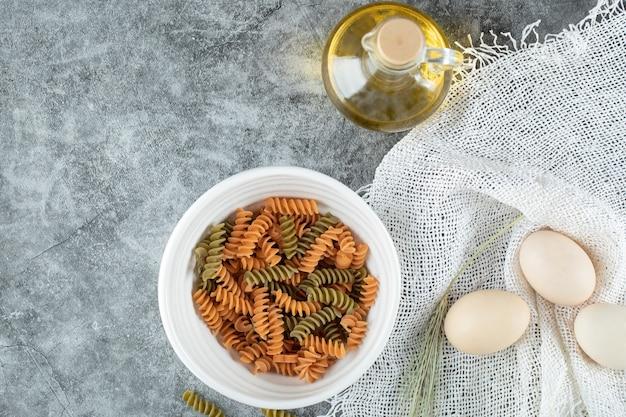 Ongekookte spiraalvormige macaroni in witte plaat met drie eieren en een fles olie