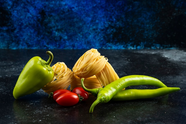 Ongekookte tagliatelle nesten en groenten op donkere tafel.
