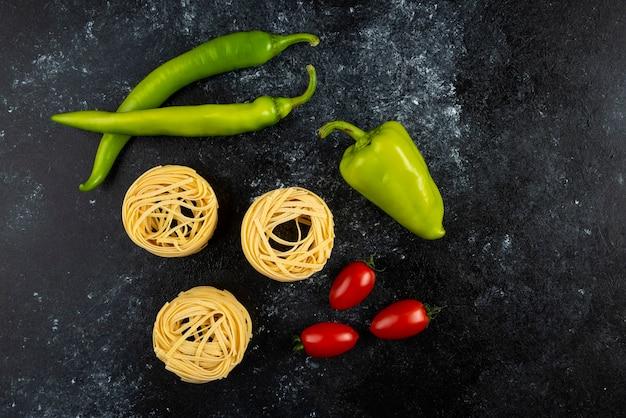 Ongekookte tagliatelle-nesten en groenten op marmer.