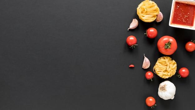 Ongekookte tagliatelle pasta met teentje knoflook; tomaat; en saus over zwarte achtergrond
