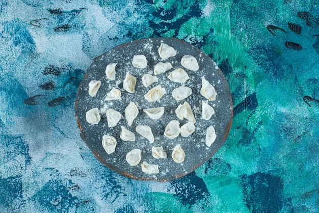 Ongekookte turkse ravioli op een bord, op de blauwe achtergrond.